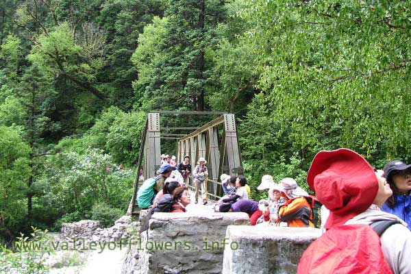 Bridge over Pushpawati River, some Japanese are taking rest while coming back from Valley of Flowers