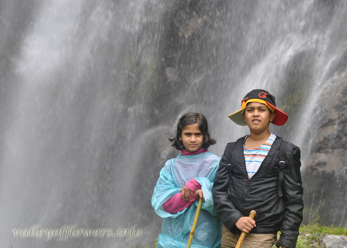 Me and My Sister near a waterfall at the entrance of Valley of Flowers